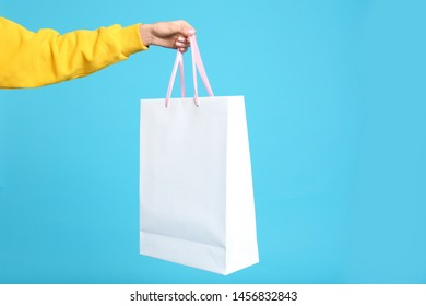 Young woman holding paper bag on blue background, closeup