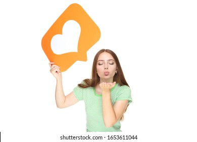 Young woman holding paper card with heart and sending kiss on white background