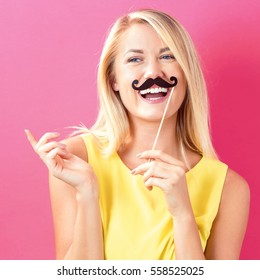 Young woman holding paper party sticks on a pink background