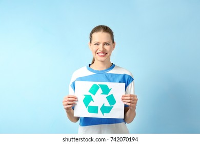 Young woman holding paper sheet with recycling symbol on color background