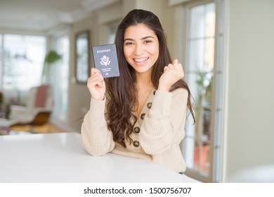 Young woman holding passport of United States of America screaming proud and celebrating victory and success very excited, cheering emotion