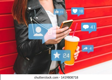Young woman holding phone with icon notification.Social media or social network concept.