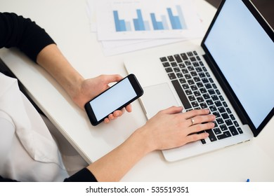 Young woman holding a phone. Workplace near the window with laptop. Close up