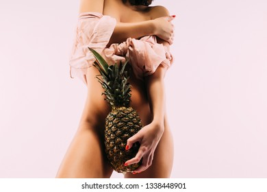 Young  woman holding a pineapple in her hand