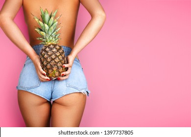 Young woman holding a pineapple in her hand on purple background.