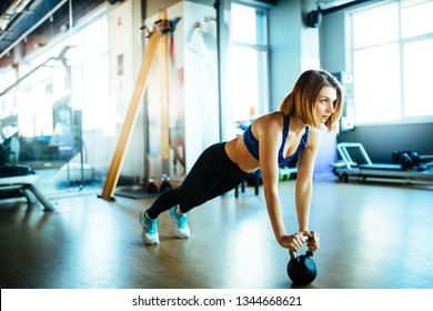 Young woman holding a plank on a kettlebell in a gym