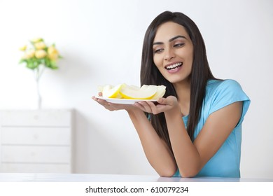 Young woman holding plate with slices of melon at home