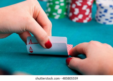 Young woman holding pocket aces poker cards in front of gambling chips. Close up, detail on cards