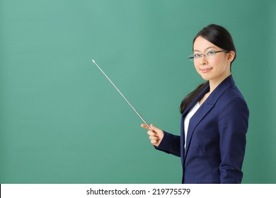 young woman holding pointer against green background
