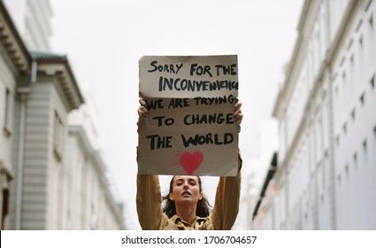 Young woman holding poster and protesting. Demonstrator making protest about climate change.