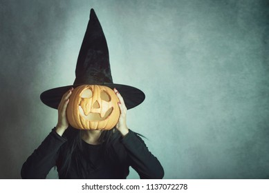 Young woman holding a pumpkin in halloween