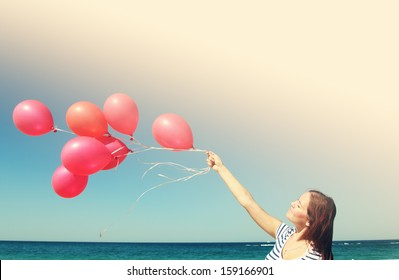 Young woman holding red balloons. Photo in old color image style.