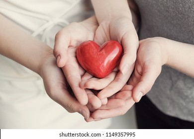 Young woman holding red heart, health insurance, donation concept