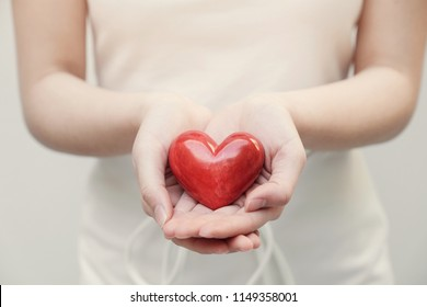Young woman holding red heart, health insurance, donation concept, world health day