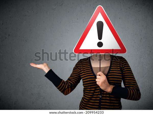 Young woman holding a red traffic triangle warning sign in front of her head