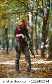 Young woman holding rifle in the hands of the autumn forest