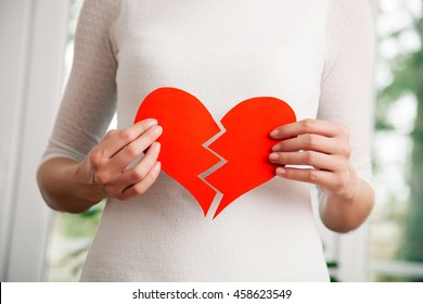 Young woman holding ripped heart shaped paper, close up