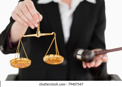 Young woman holding scales of justice and a gavel with the camera focus on the scales against a white background