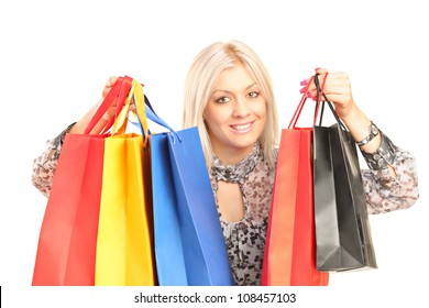 Young woman holding shopping bags, isolated on white background