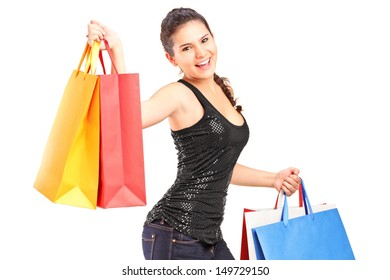 Young woman holding shopping bags isolated against white background