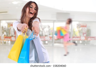 young woman holding shopping bags in front of the store