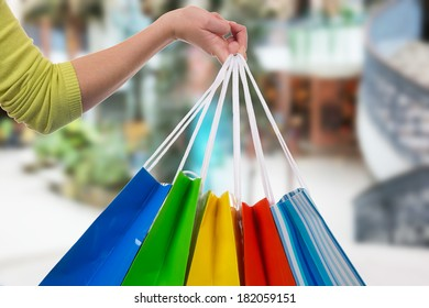 Young woman holding shopping bags in her hand in a shopping mall