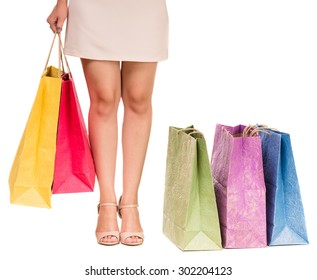 Young woman holding shopping bags on white background. Colored shopping bags on the floor. Close-up.