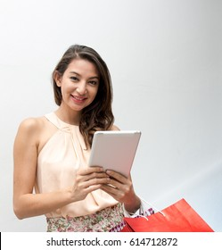 Young woman holding shopping bags and a mobile phone, Beautiful woman looking at her  tablet while carrying gift bags,Age 30-40 years