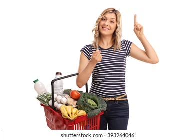 Young woman holding a shopping basket full of groceries and having an idea isolated on white background