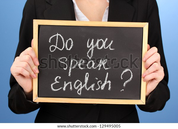 """Young woman holding sign """"Do you speak English?"""""""