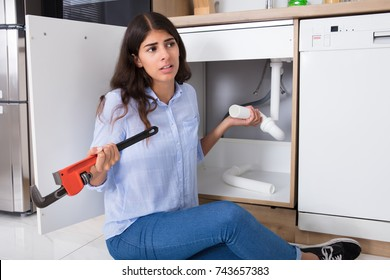 Young Woman Holding Sink Pipe And Monkey Wrench In Kitchen
