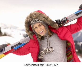Young Woman holding Skis In Alpine Landscape