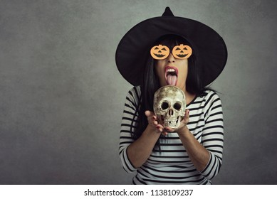 Young woman holding a skull in halloween