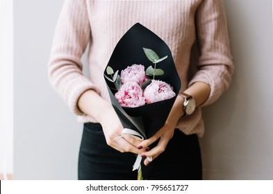 Young woman holding a small beautiful blossoming peonies flower bouquet on the grey wall background, cropped photo