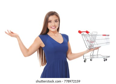 Young woman holding small shopping cart on white background