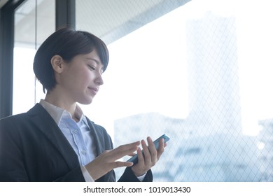 Young woman holding smart phone in the office.