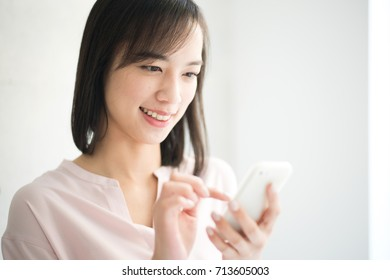 Young woman holding smart phone.