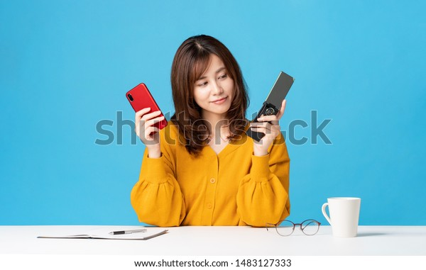 Young woman holding a smart phone and a feature phone.