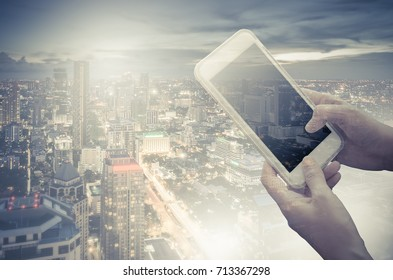 Young woman holding smartphone in hand while typing, double exposure with modern city skyline, vintage style process