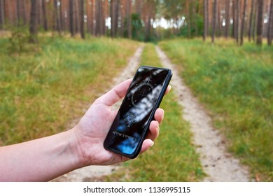 Young woman holding a smartphone and looking for a route in a navigation application with compass, on a forest path in nature