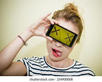 Young woman holding smartphone over eyes with two X symbols on display pretending dead, concept.