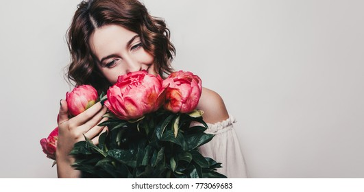 Young woman holding and smell bouquet of beautiful pink peonie flowers. International woman Day 8 march concept border