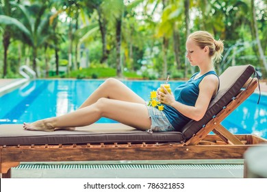 Young woman is holding a smoothie of mango on the background of the pool. Fruit smoothie - healthy eating concept. Close up of detox smoothie with mango.