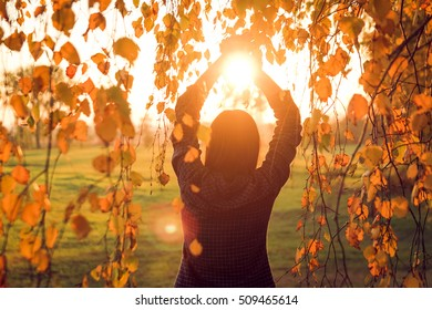 Young woman holding sun with her hands and watching beautiful autumn sunset