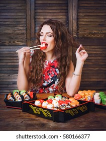 Young woman holding sushi with a chopsticks. Woman with perfect make up holding sushi roll.
