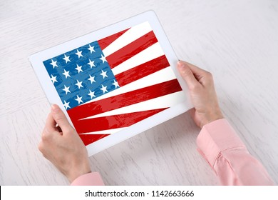 Young woman holding tablet with American flag on screen over table