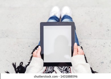 Young woman holding a tablet with blank screen in hand top view.