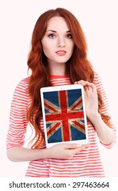 Young woman holding tablet PC with a grunge British national flag on screen. Separated on white background. English language learning concept