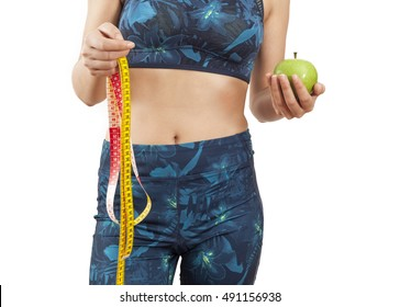 Young woman holding tape measure and apple