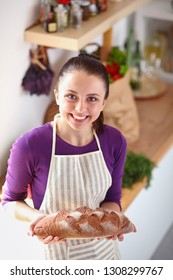 Young woman holding tasty fresh bread in her kitchen . Young woman. fresh bread